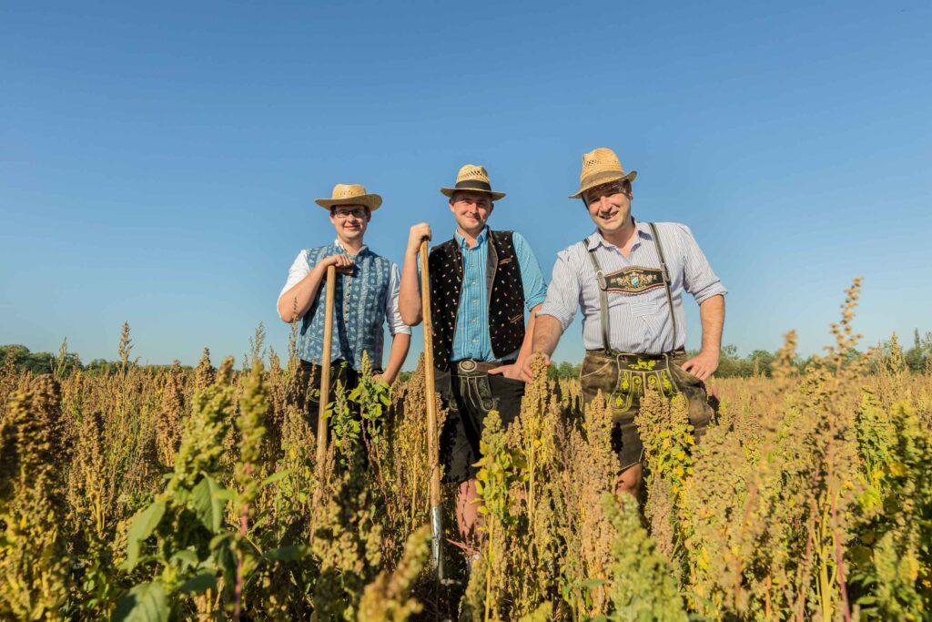 Drei Bauern lachend auf einem Quinoa Feld